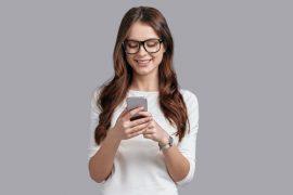 Vrouw met bril kijkt naar smartphone
