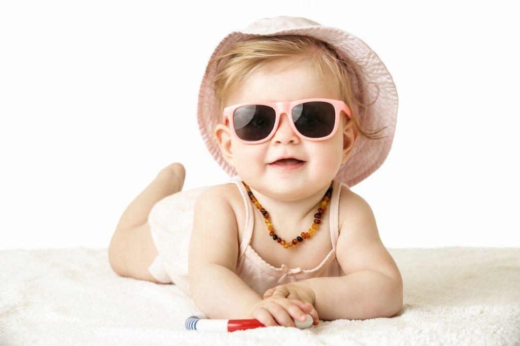 Baby met zonnebril en zonnehoed