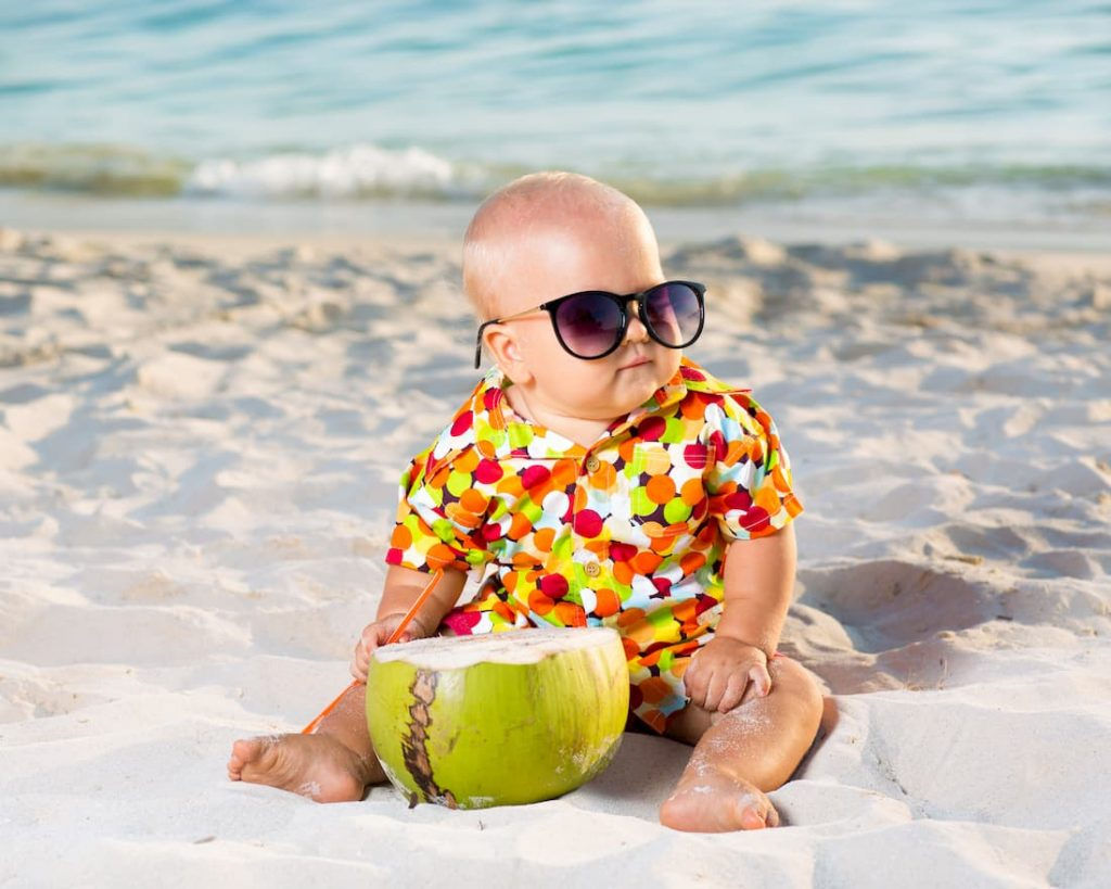 Baby draagt zonnebril op het strand