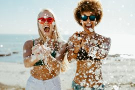 2 dames dragen zonnebrillen op het strand tijdens vakantie