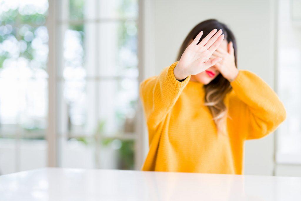Vrouw houdt handen voor haar ogen vanwege fotofobie