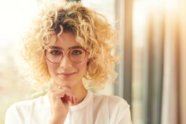 vrouwmetbrilkijktindecamera